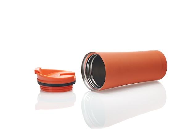 Oranje reismok geïsoleerd op een witte achtergrond. herbruikbare koffiekop om mee te nemen. thermosfles van roestvrij staal met schuifvergrendeling. beker en thermoskan. mokkenmodel voor koude en warme dranken