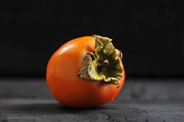 Oranje rijpe dadelpruim op zwarte