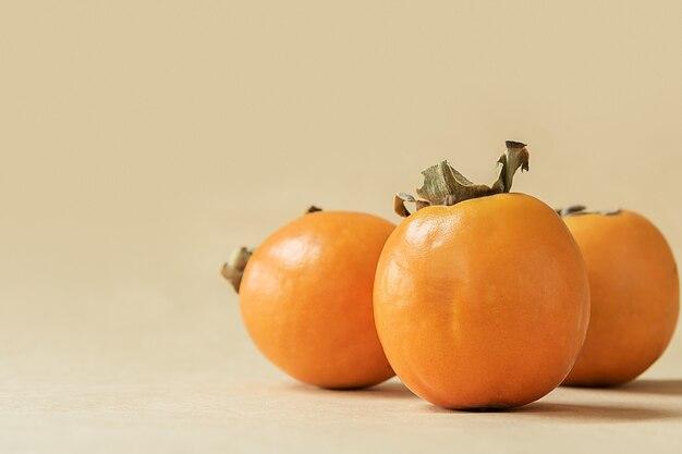 Oranje rijpe persimmon op pastel beige achtergrond.