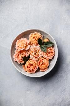 Oranje rozen die in water op beton drijven