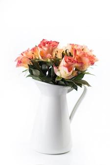 Oranje rozen in witte kruik geïsoleerd