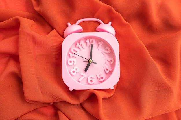 Oranje sjaal en wekker textuur achtergrond, minimaal concept idee.