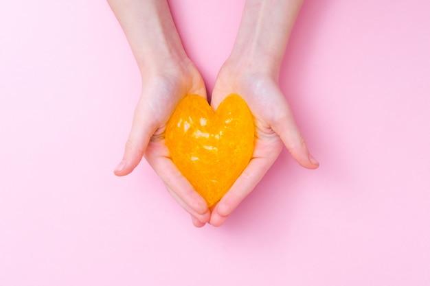 Oranje slijm in hartvorm in kinderhanden. het meisje overhandigt het spelen slijmstuk speelgoed op roze achtergrond. slijm maken. liefde en valentijnsdag concept