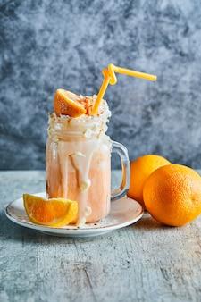 Oranje smoothie met hagelslag en stro op de witte plaat