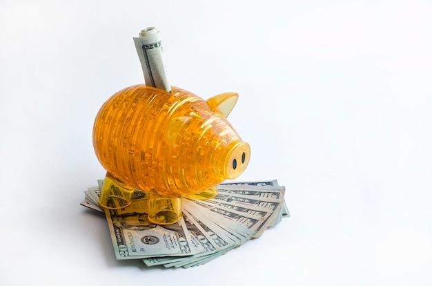 Oranje spaarvarken met amerikaanse dollarsbankbiljetten. contant geld. bedrijfs, financiën, investeringen, sparen en corruptie concept.