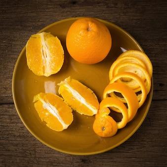 Oranje spiraal schil halve plak op schotel op oud hout