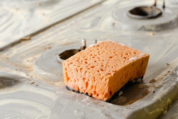 Oranje spons op vuil gasfornuis.