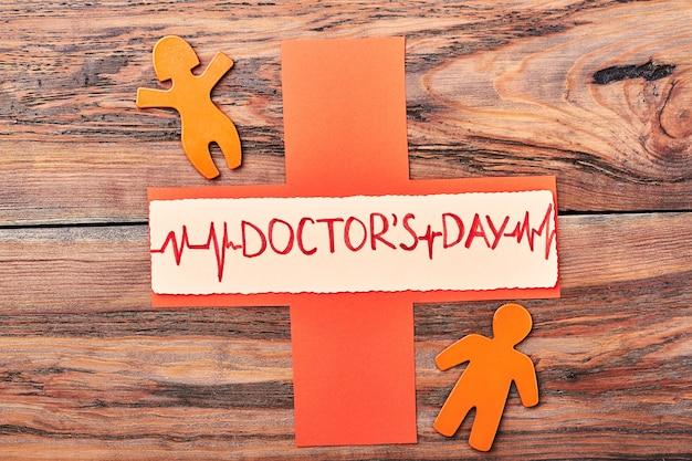 Oranje stickmen en kruis. happy doctor's day aan cardioloog.