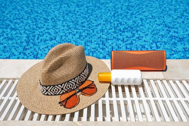 Oranje strandaccessoires, zonnebrandcrème voor het zwembad, zonnebril, hoed met muziekspeaker