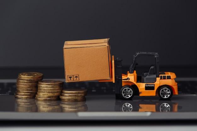 Oranje stuk speelgoed heftruck met kartondozen en muntstukken op toetsenbord