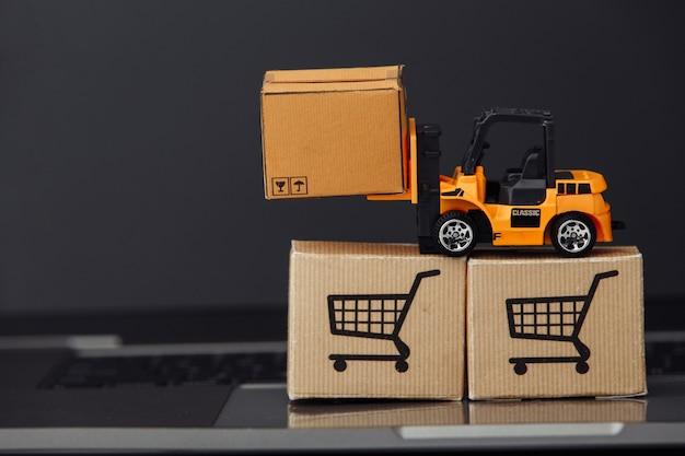 Oranje stuk speelgoed heftruck met kartondozen op toetsenbord. logistiek en groothandelsconcept