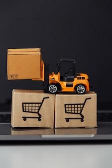 Oranje stuk speelgoed heftruck met kartondozen op toetsenbord
