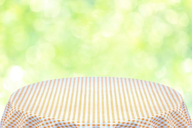 Oranje tafelkleed met groene achtergrond. achtergrond voor platte tekst of producten