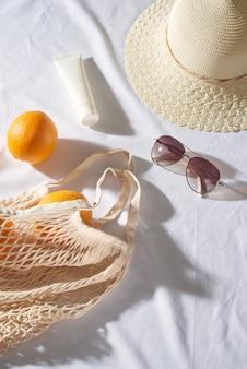 Oranje tas met bril, zonnebrandcrème, strohoed op de picknick bij zonsondergang.