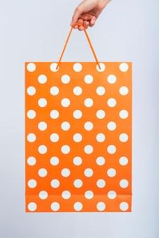 Oranje tas met witte stippen vastgehouden