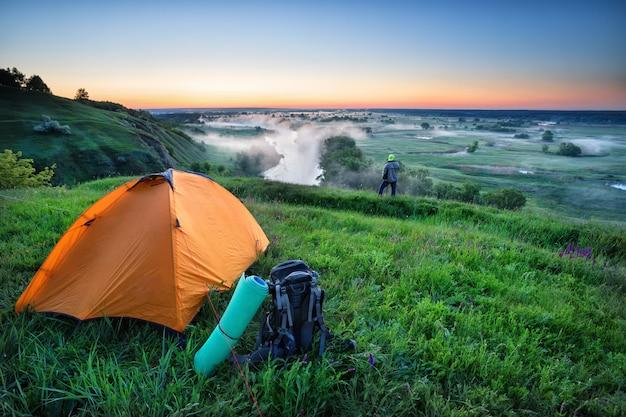Oranje tent en rugzak op heuvel met toerist
