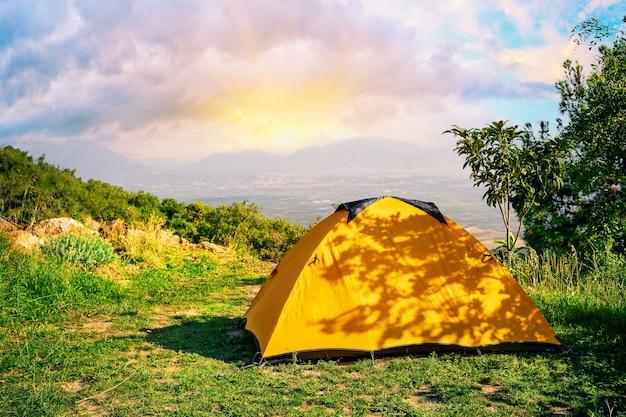 Oranje tent op een heuvel met bergen op de achtergrond bij zonsopgang