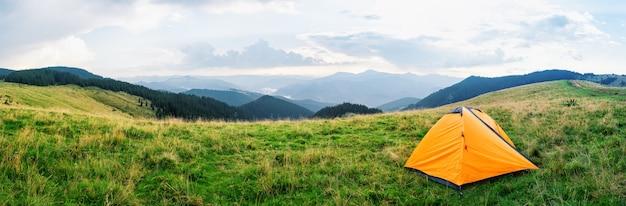 Oranje tent op een weide met groen gras in de bergen
