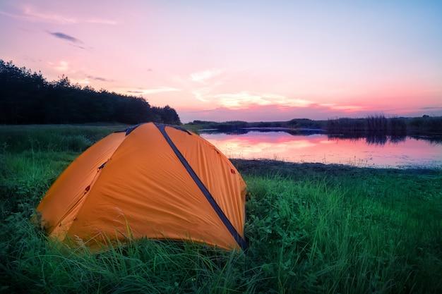 Oranje toeristische tent in groen gras op de oever van het meer