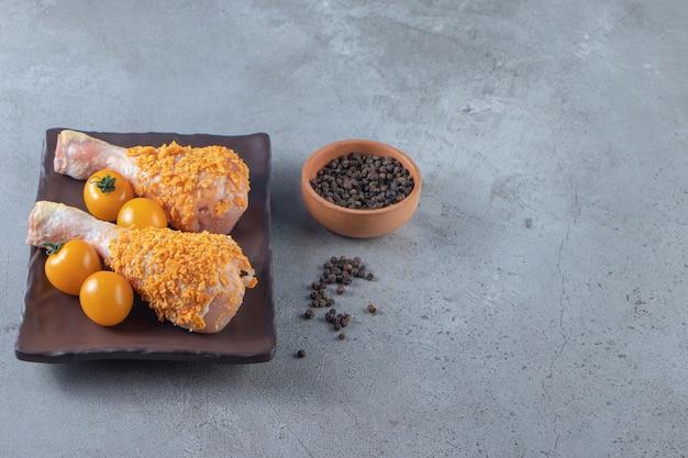 Oranje tomaten en kippentrommelstokken op een schotel naast kruidenkom, op de marmeren achtergrond.