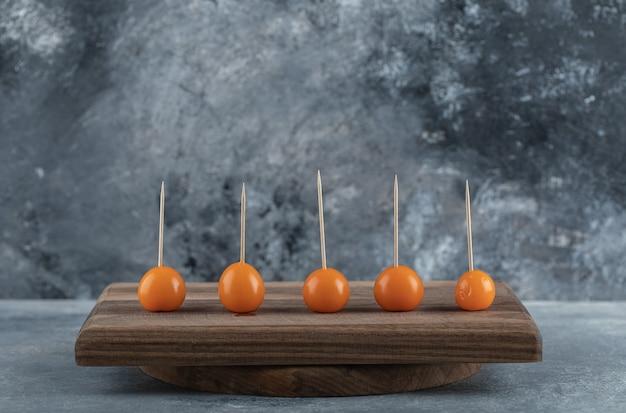Oranje tomaten met stokken op een houten bord.
