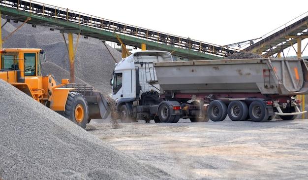 Oranje tractor en grijze vrachtwagen geladen met grind