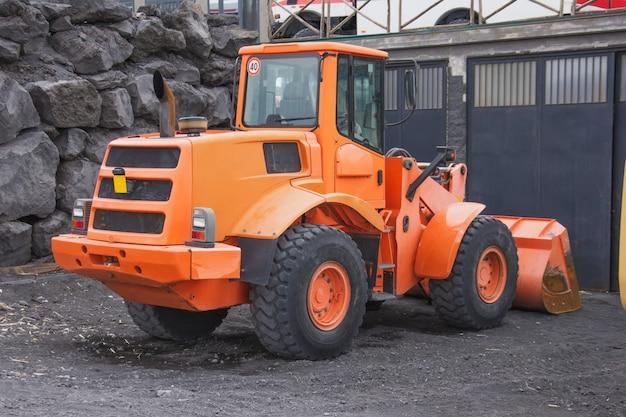 Oranje tractor met een emmer vooraan geparkeerd in de bergen.