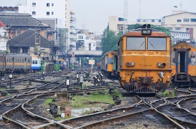 Oranje trein locomotief bangkok railway station thailand met spoorweg kruising.
