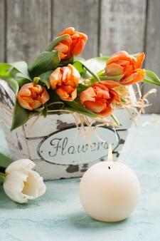 Oranje tulpen in houten mandje en verlichte cadle