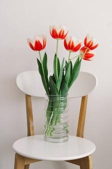 Oranje tulpen op een witte stoel in de woonkamer. lente en feestdagen.