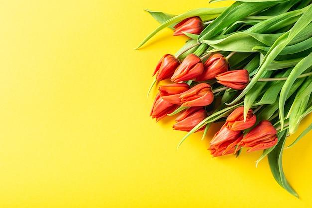 Oranje tulpen over geel oppervlak, pasen. verjaardag, moederdag wenskaart concept met kopie ruimte. bovenaanzicht, plat gelegd