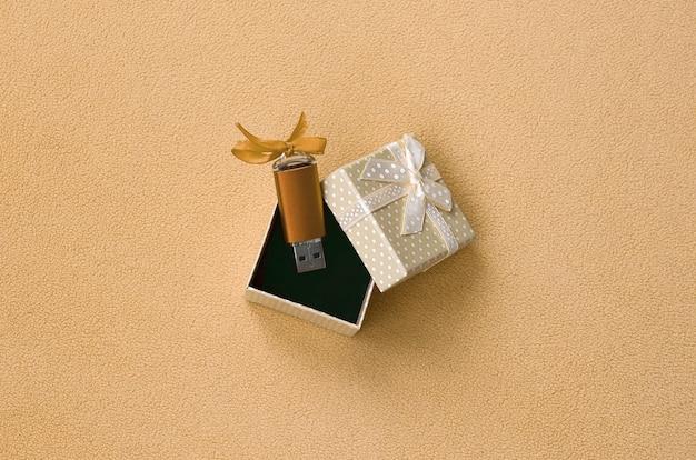 Oranje usb flash-geheugenkaart met een boog ligt in een kleine geschenkverpakking