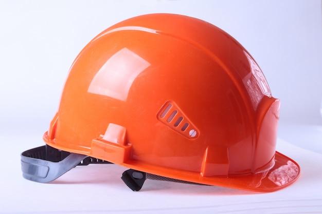 Oranje veiligheidshelm, die op witte achtergrond wordt geïsoleerd.