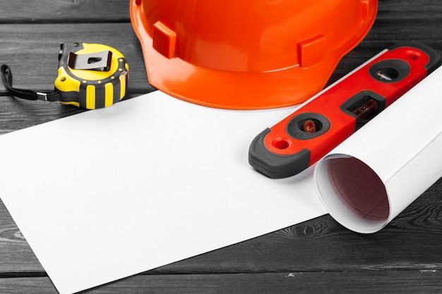 Oranje veiligheidshelm en verscheidenheid aan reparatiehulpmiddelen over houten achtergrond