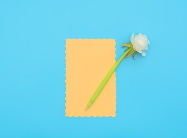 Oranje vel papier met groene pen met witte bloem erop op blauwe achtergrond.