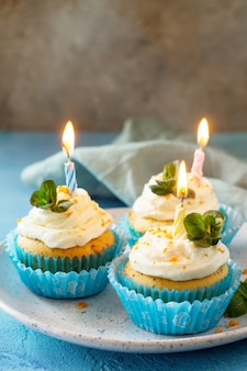 Oranje verjaardagscupcake met buttercream icing en kaars kopieer de ruimte