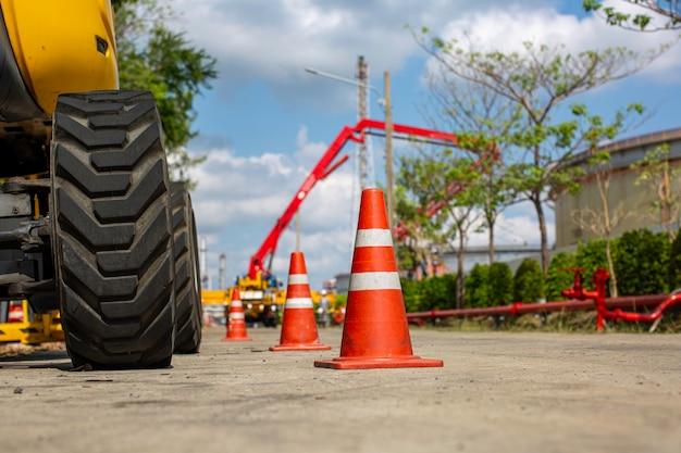 Oranje verkeerskegel op parkeerplaats in de buurt van hydraulische kraanvorkheftruck.