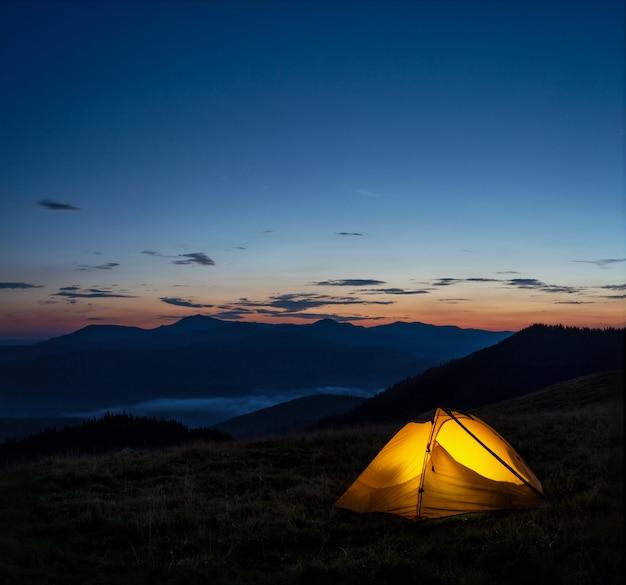Oranje verlichte tent in bergen onder avondhemel