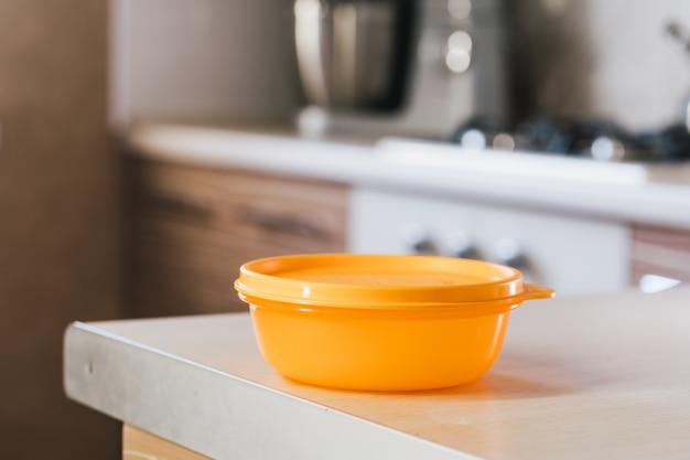 Oranje voedsel opslag container op tafel
