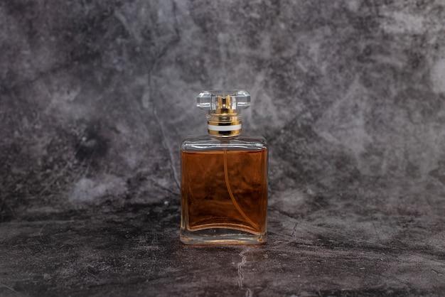 Oranje vrouwenparfum op donkere achtergrond