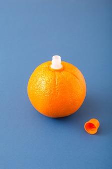 oranje waarop zich een sapstop bevindt en een deksel aan de zijkant op een blauwe achtergrond. voedsel citrusvruchten stilleven concept.