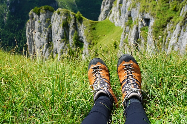 Oranje wandelschoenen van de vrouw tegen een met gras begroeide grond met uitzicht op rotsachtige bergen