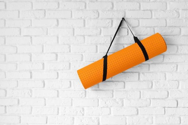 Oranje yogamat die op muur hangt