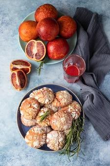 Oranje zandkoek crinkle cookies met poedersuiker, rozemarijn en siciliaanse bloedsinaasappelen