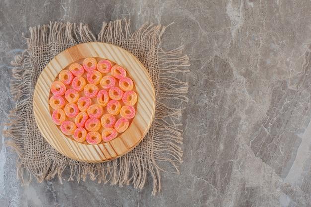 Oranje zoete snoepjes in ringvorm op houten plaat over zak.