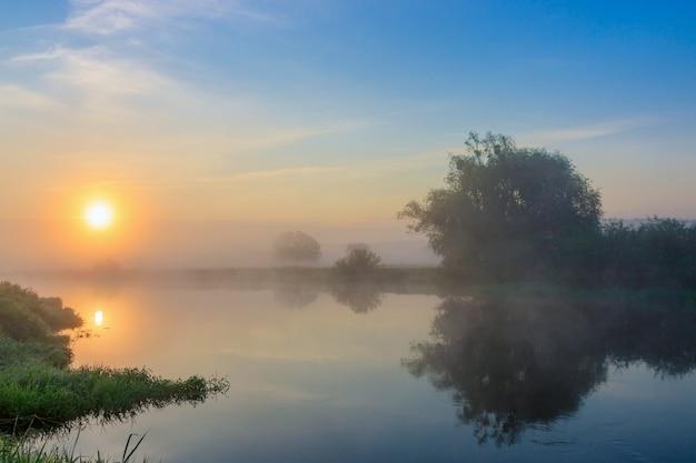 Oranje zon over rivieroppervlak met mist in zomerochtend. rivierlandschap