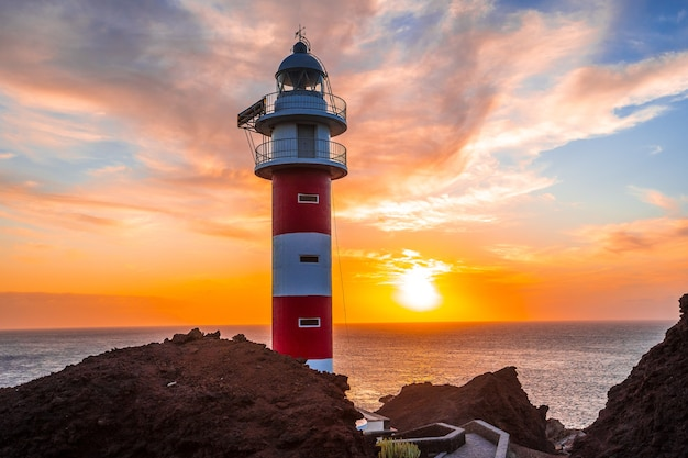 Oranje zonsondergang bij de vuurtoren van punta de teno op het eiland tenerife, canarische eilanden. spanje