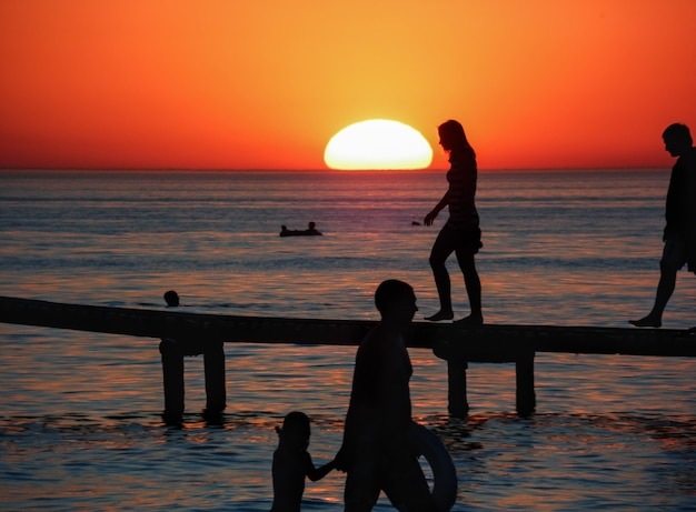 Oranje zonsondergang op de zee met silhouetten van mensen op vakantie op de pier.