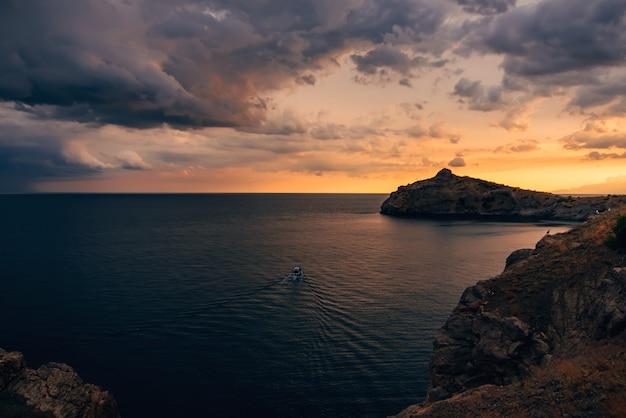 Oranje zonsondergang op zee met bergen