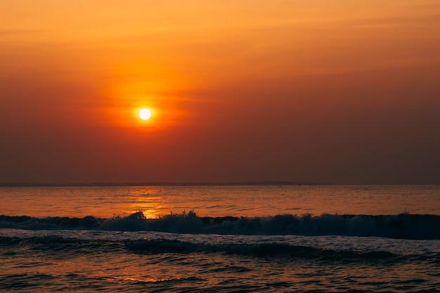 Oranje zonsopgang tegen de zee met golven